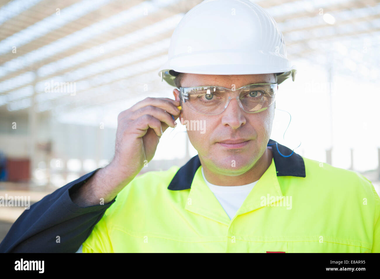 Builder with safety glasses inserting earplugs on construction site - Stock Image