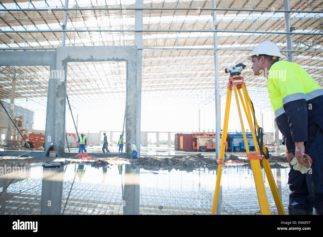 Surveyor using tripod and level on construction site - Stock Image