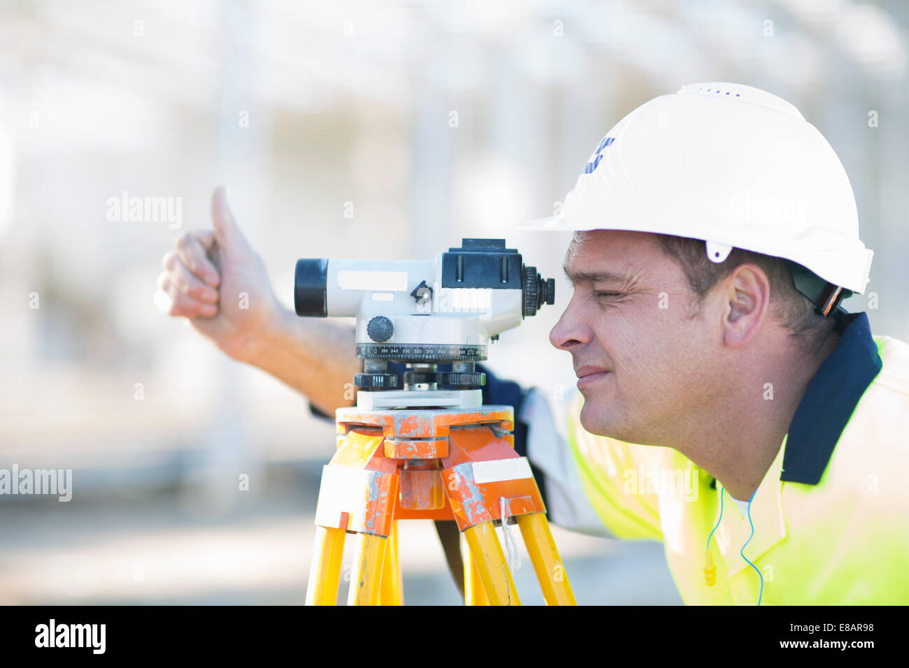 Surveyor looking through level on construction site - Stock Image