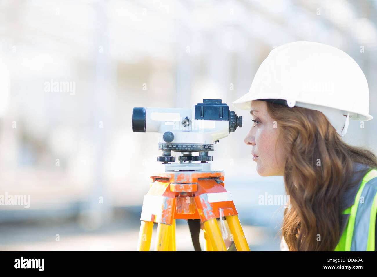 Female surveyor looking through level on construction site - Stock Image
