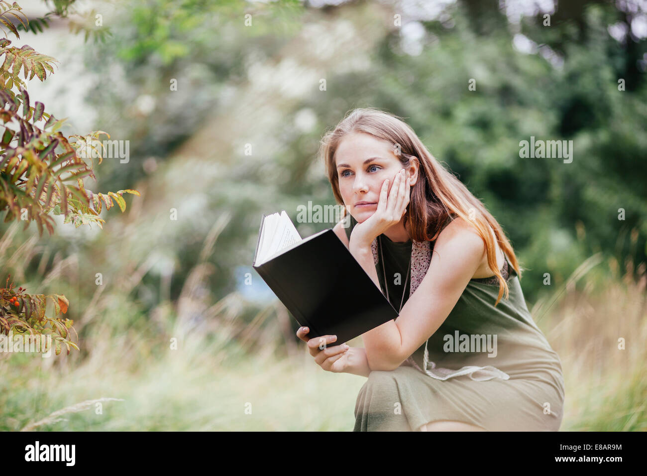 Young woman with chin on hand reading book in field - Stock Image