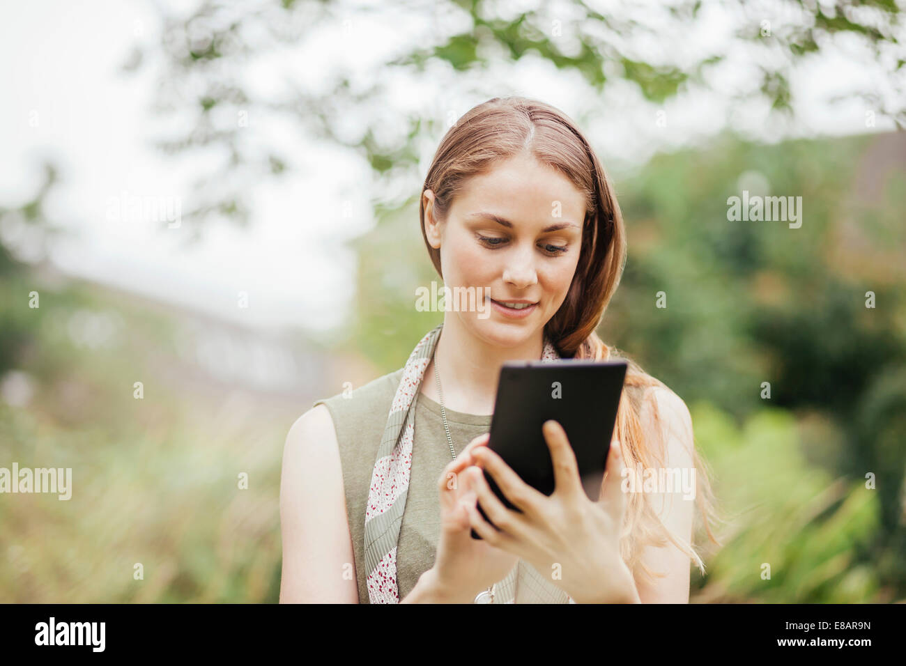 Young woman using touchscreen on digital tablet in field - Stock Image
