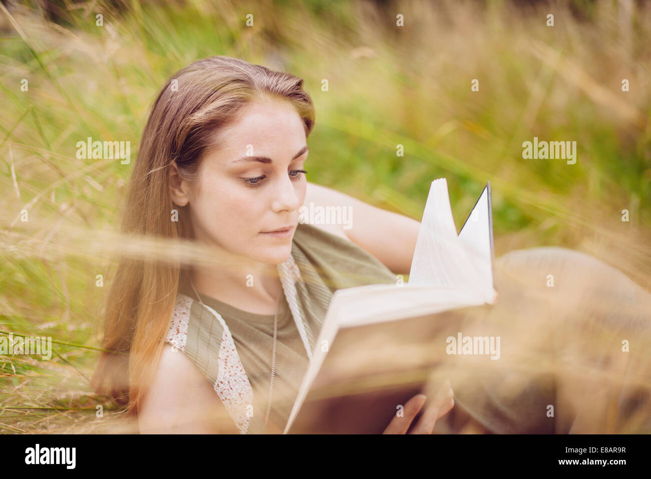 Young woman sitting in long grass reading book - Stock Image