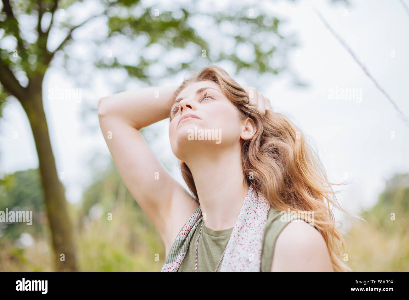 Serene young woman gazing up with hand in hair - Stock Image