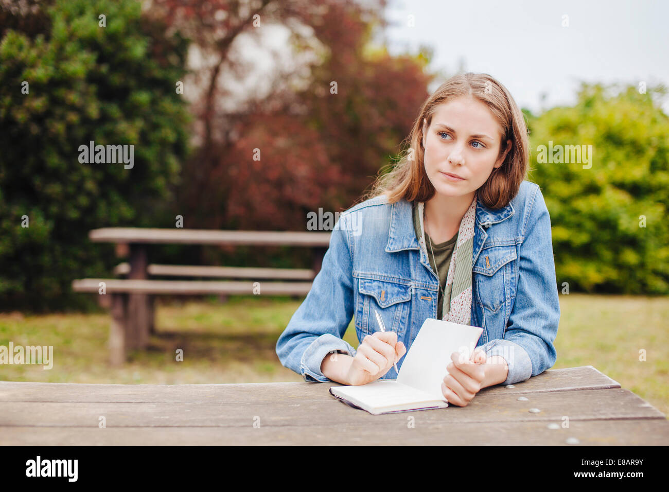 Young woman sitting at picnic bench in park writing in notebook - Stock Image