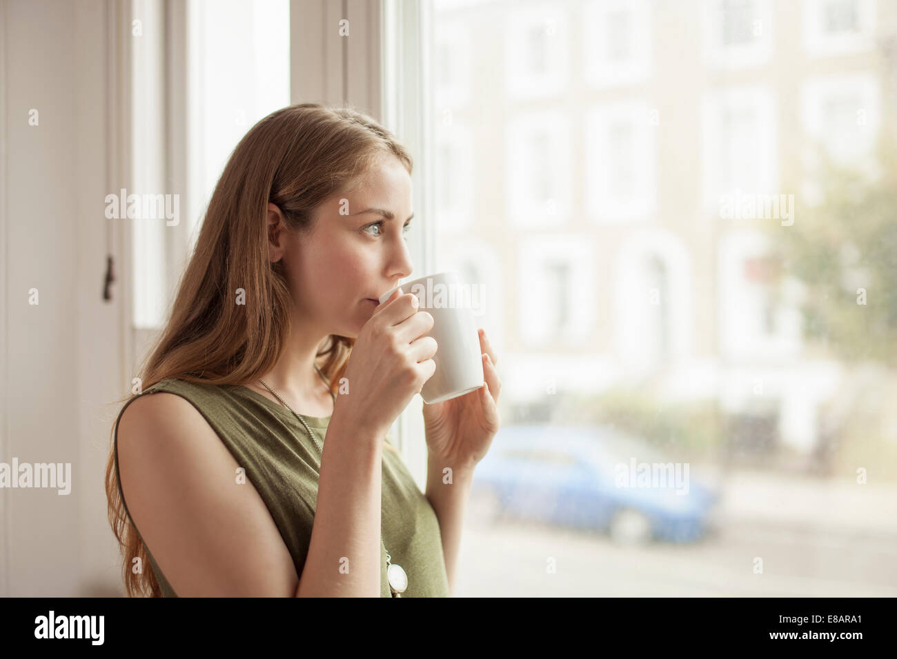 Young woman drinking coffee and gazing through sitting room window - Stock Image