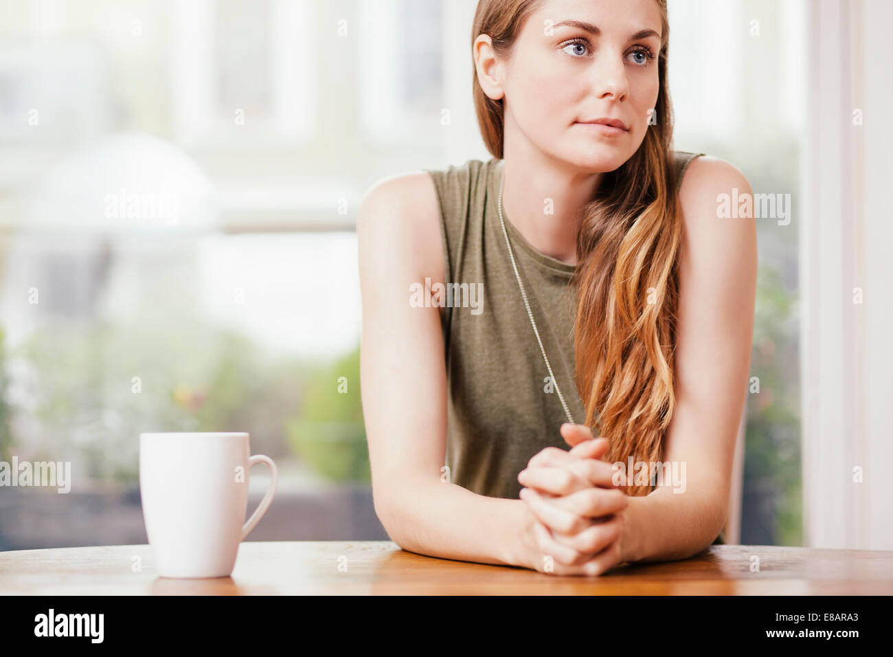 Young woman sitting with hands clasped at dining room table - Stock Image