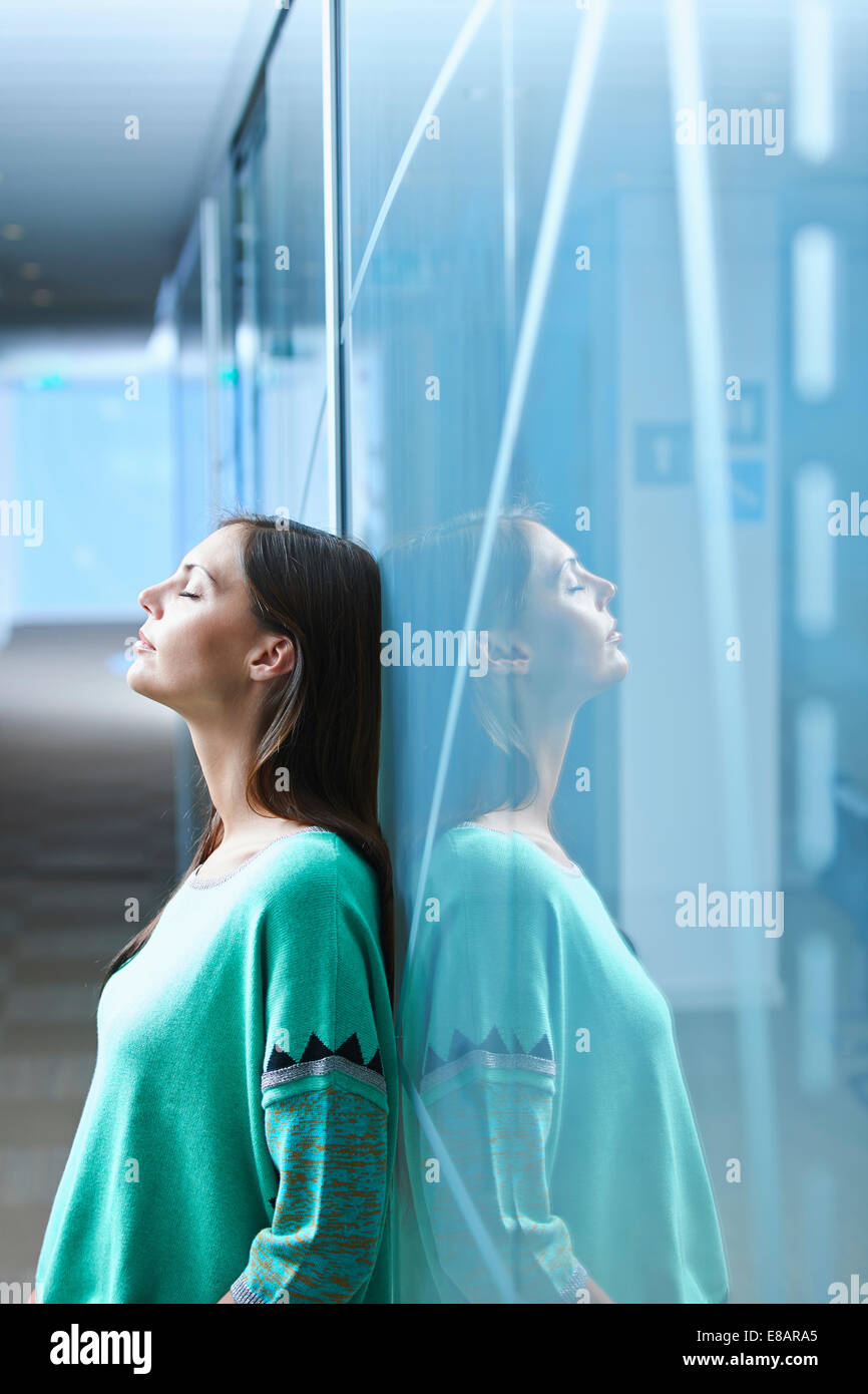 Mid adult businesswoman leaning against glass wall in office with eyes closed - Stock Image