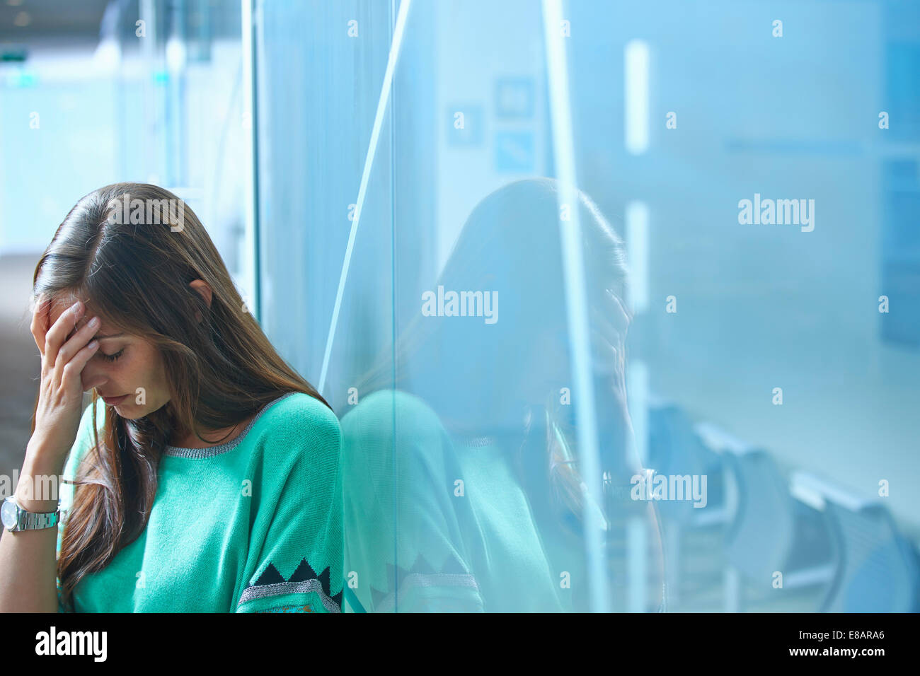 Mid adult businesswoman leaning against glass wall in office with hand on face - Stock Image