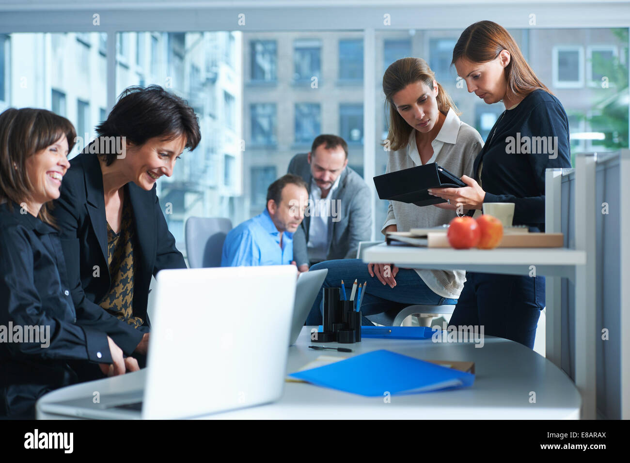 Six businesswomen and men working in busy office - Stock Image