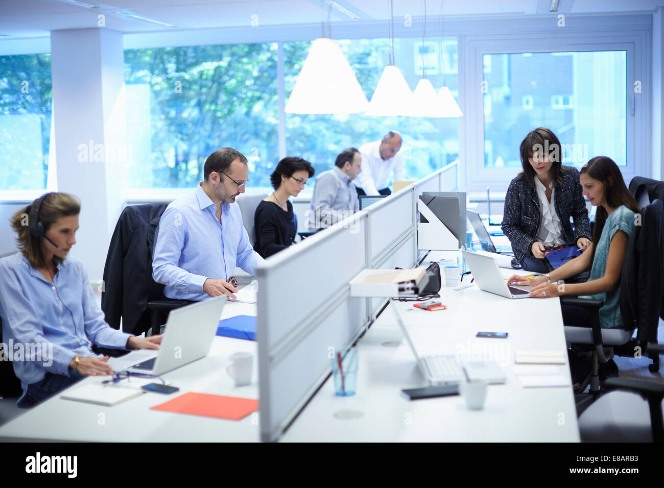 Business team at their desks in busy office - Stock Image