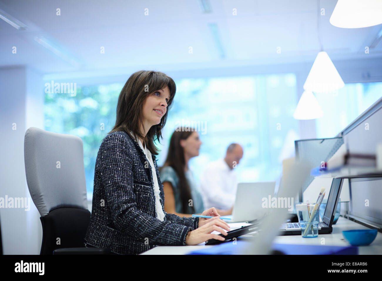 Office workers at their desks in busy office - Stock Image