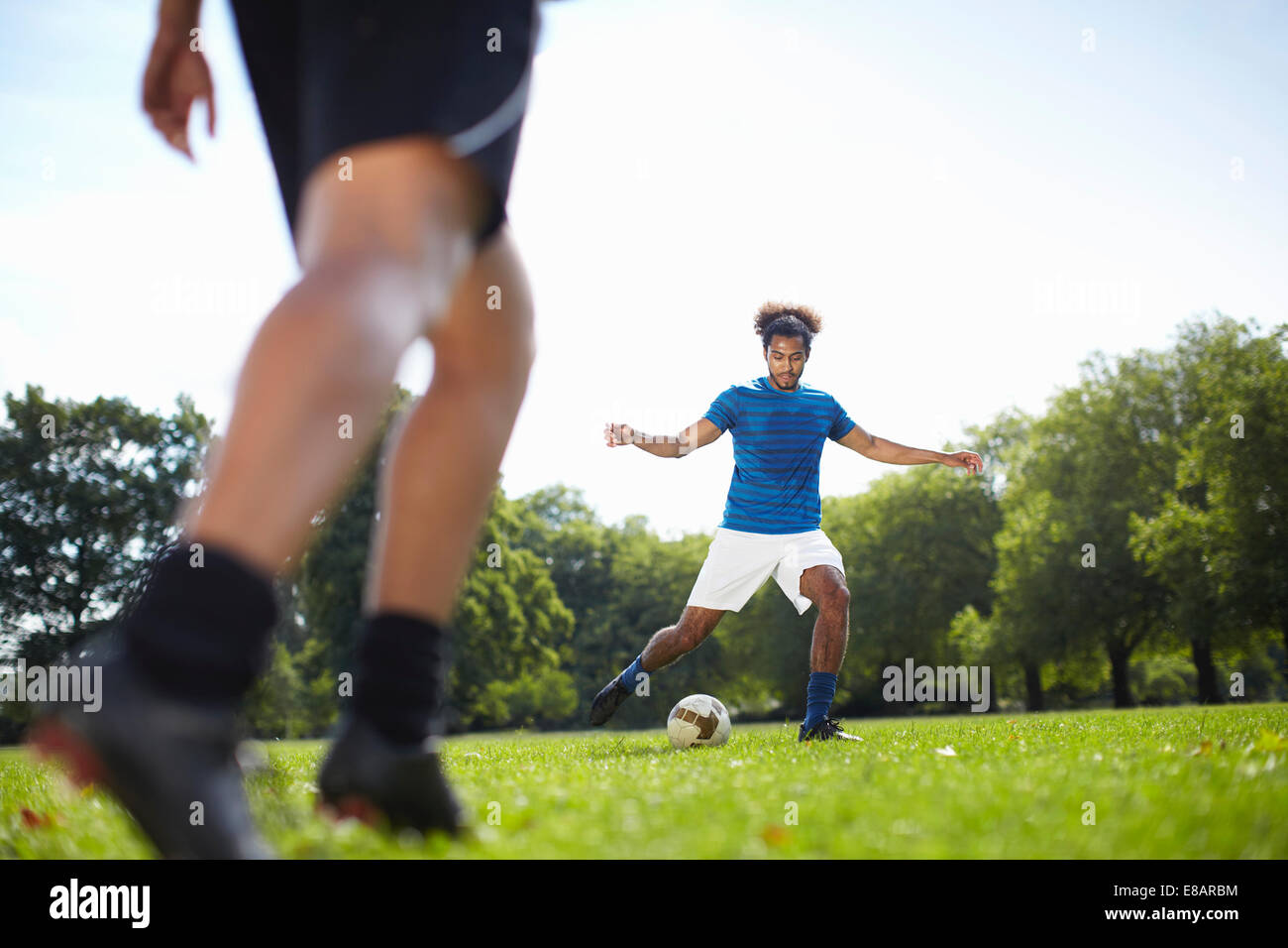 Young couple playing football together in park Stock Photo