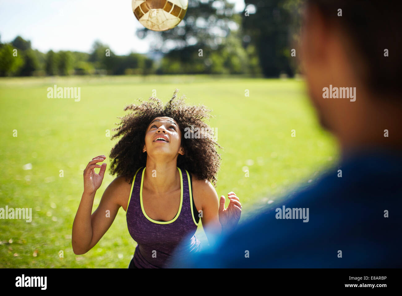Young woman heading football in park - Stock Image