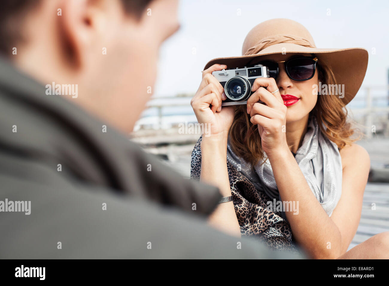 Young woman photographing boyfriend on coastal pier, Cape Town, Western Cape, South Africa - Stock Image