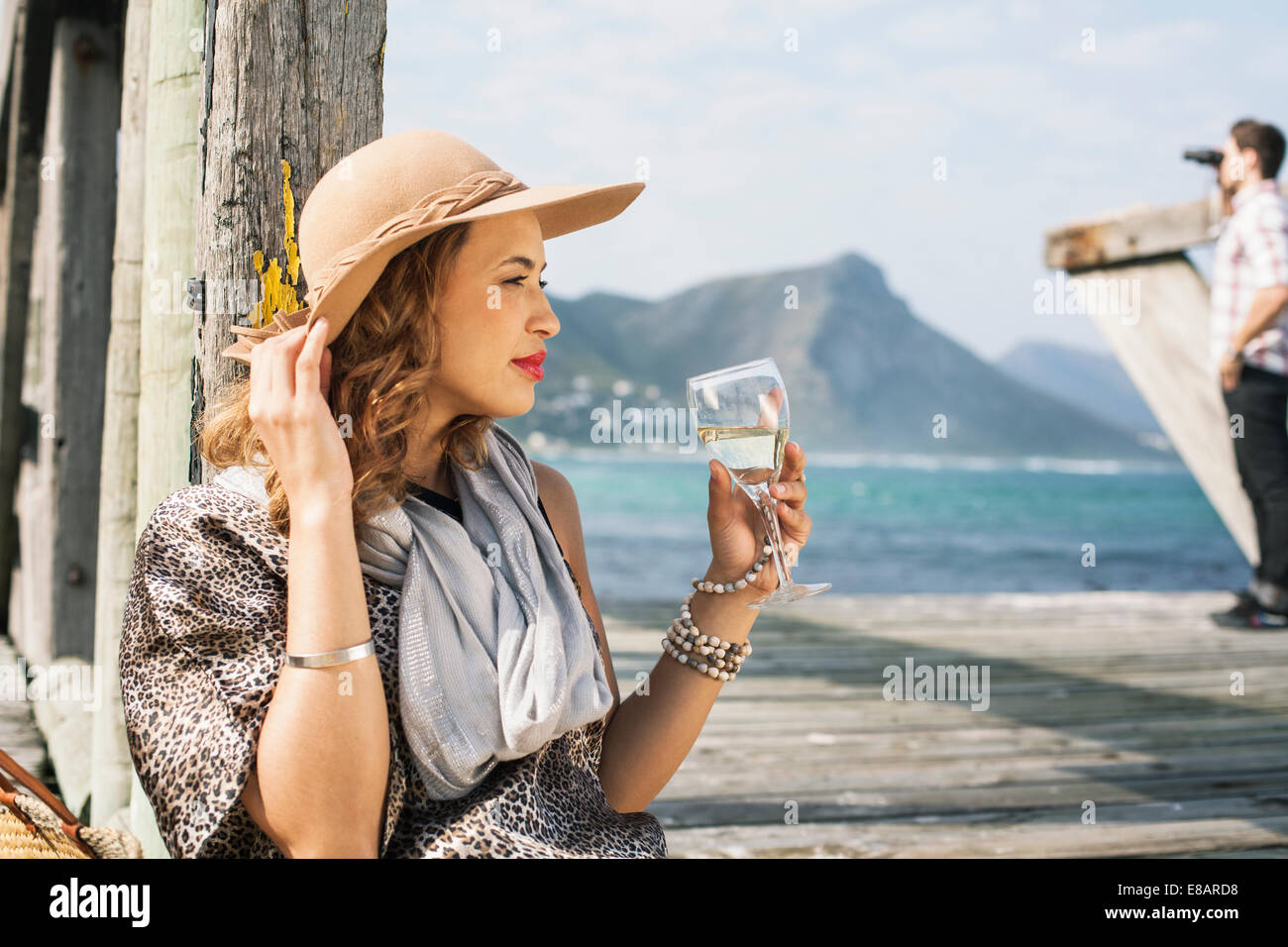 Young glamorous woman drinking wine on coastal pier, Cape Town, Western Cape, South Africa - Stock Image