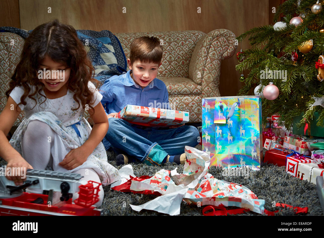 Sister and brother in sitting room unwrapping and playing with christmas gifts - Stock Image