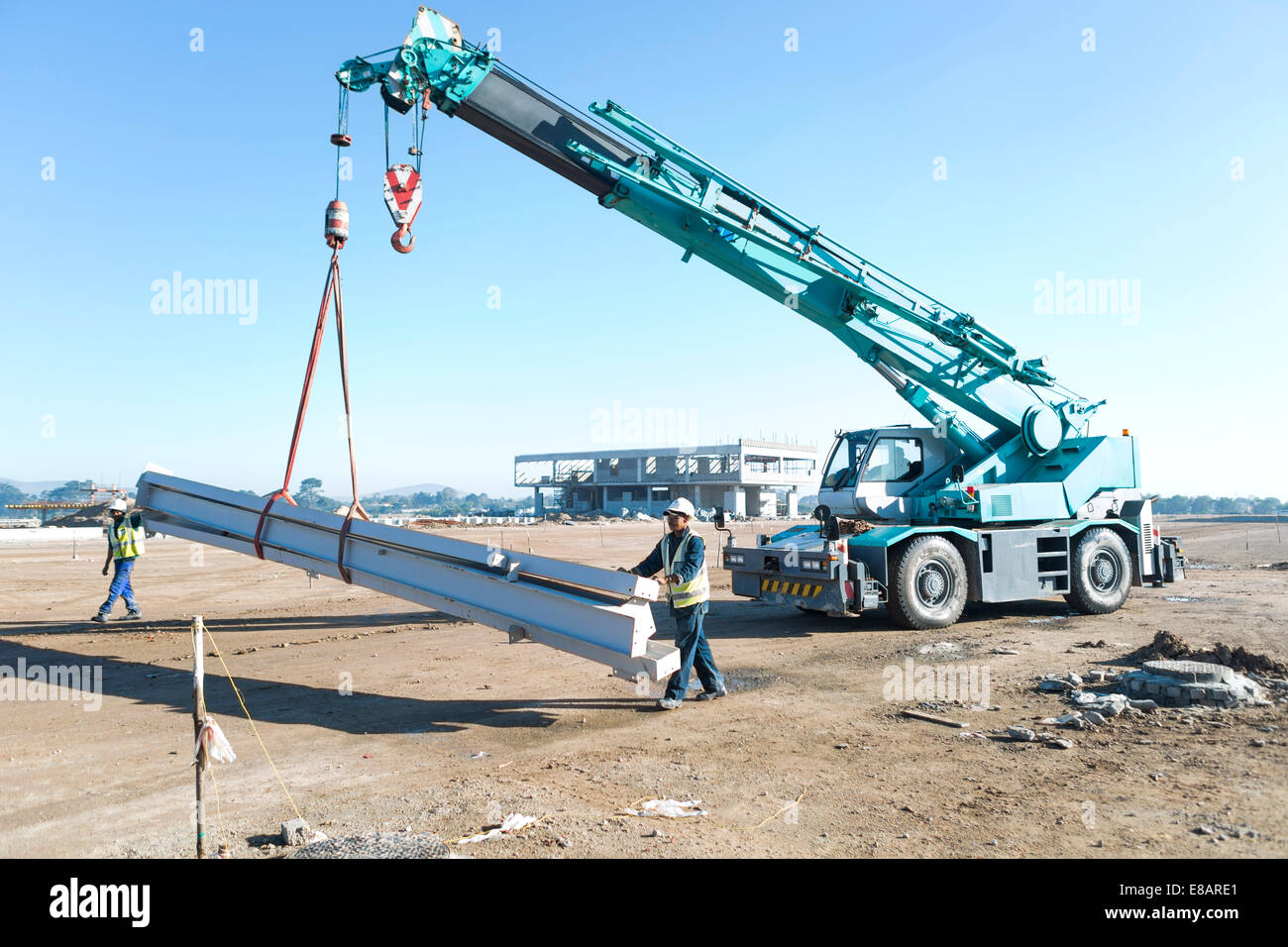 Two builders guiding girders on crane at construction site - Stock Image