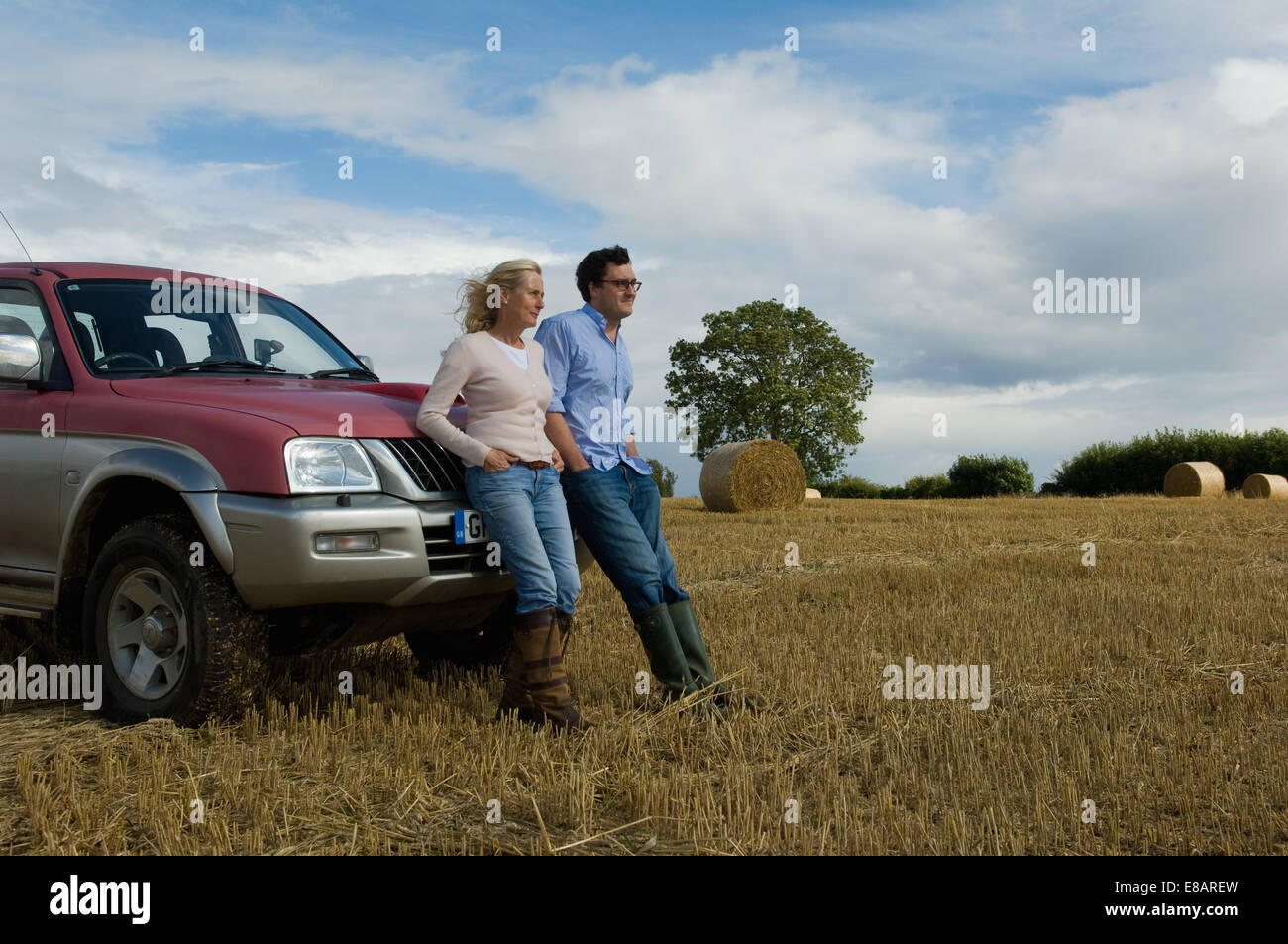 Mother and son leaning against four wheeled drive in harvested field - Stock Image