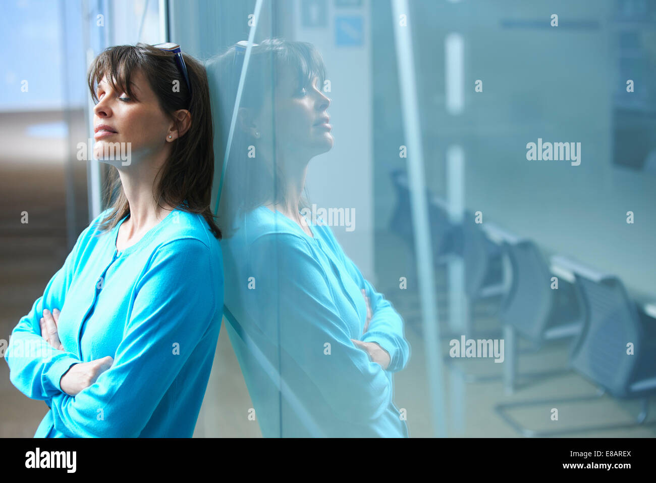 Mature businesswoman leaning against glass wall in office with eyes closed - Stock Image