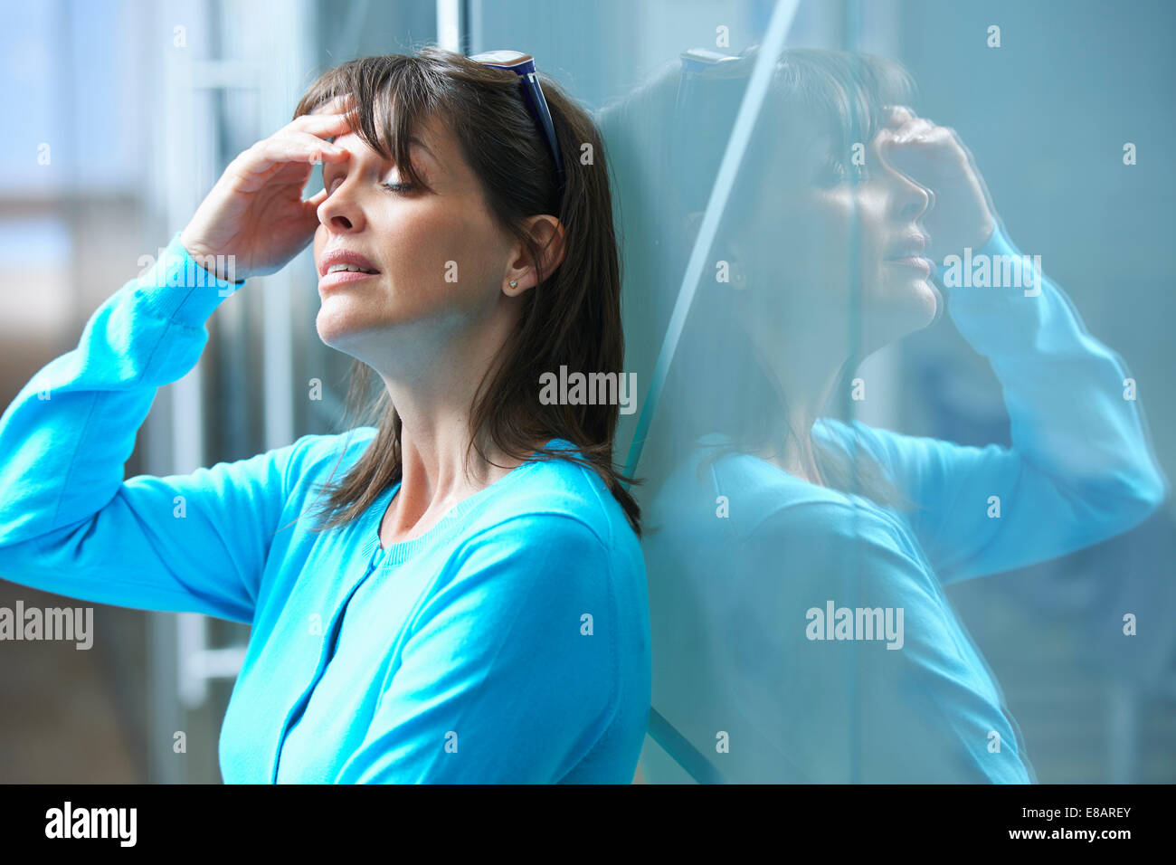 Mature businesswoman leaning against glass wall in office with hand on face - Stock Image