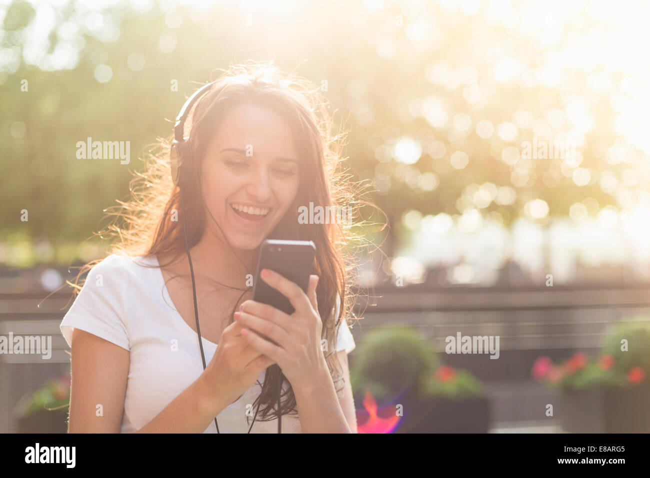 Young woman wearing headphones listening to music - Stock Image
