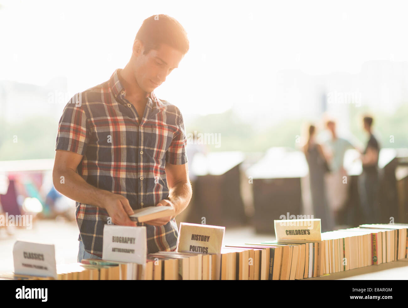 Young man at second hand book stall - Stock Image