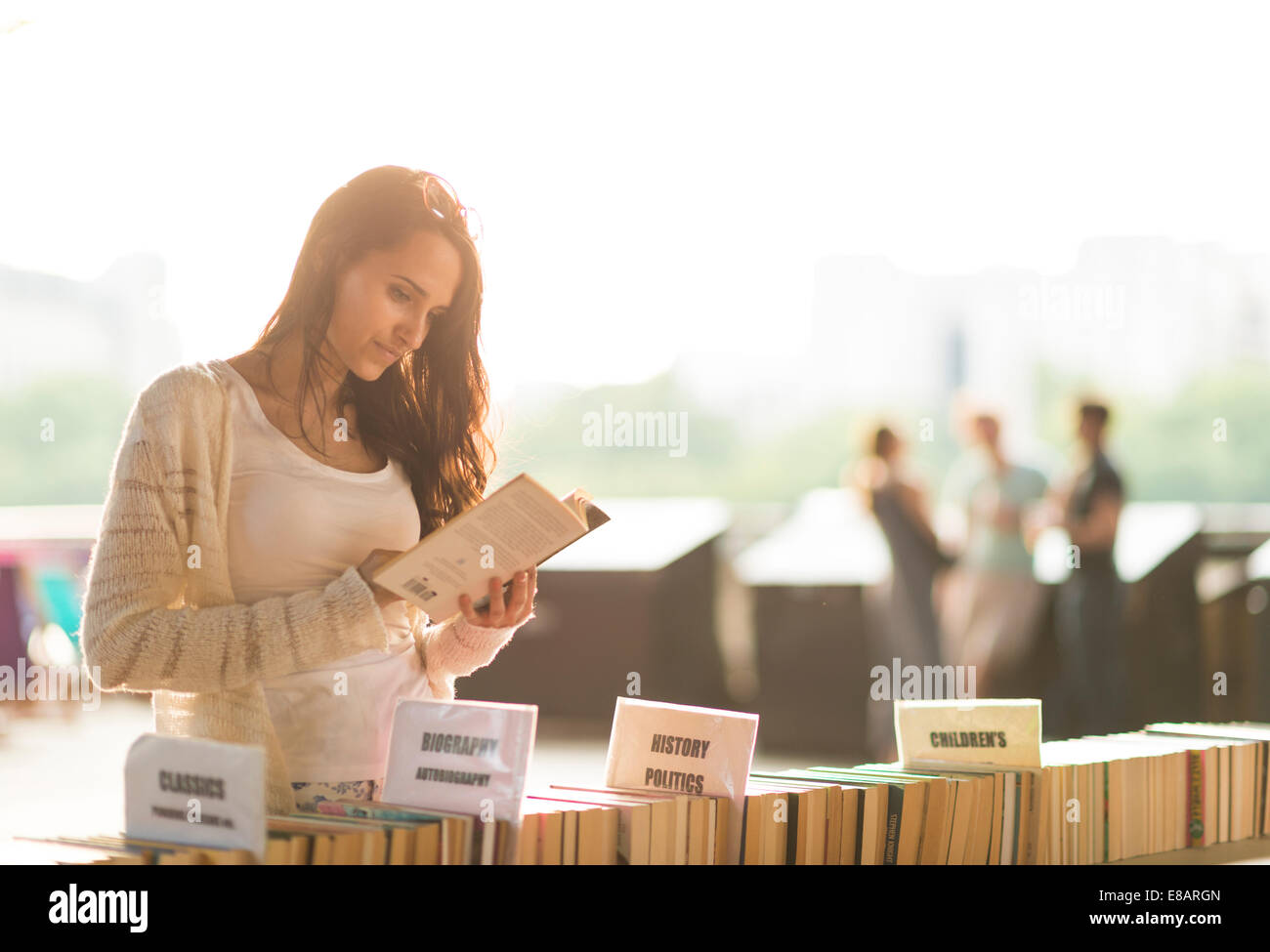 Young woman at second hand book stall - Stock Image