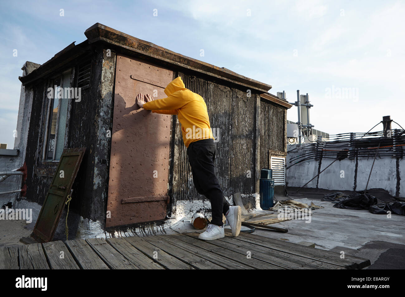 Young man leaning against rooftop hut and looking down - Stock Image