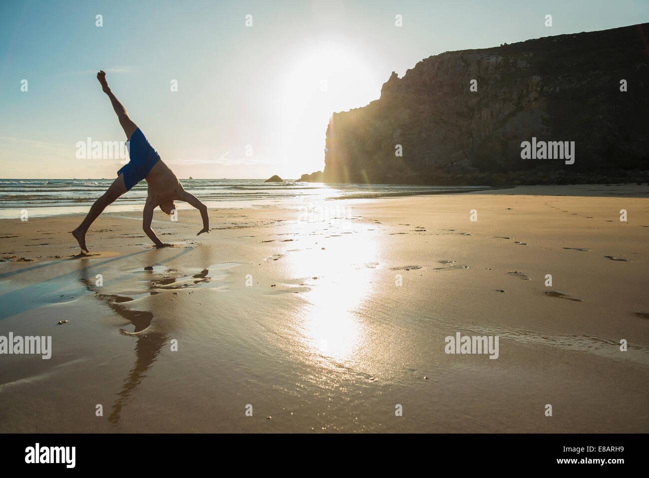 Teenage boy doing handstand on beach, Camaret-sur-mer, Brittany, France - Stock Image