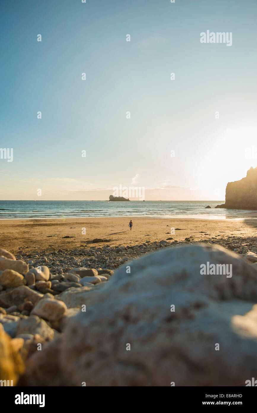 Distant view of male teenage surfer walking on beach, Camaret-sur-mer, Brittany, France - Stock Image