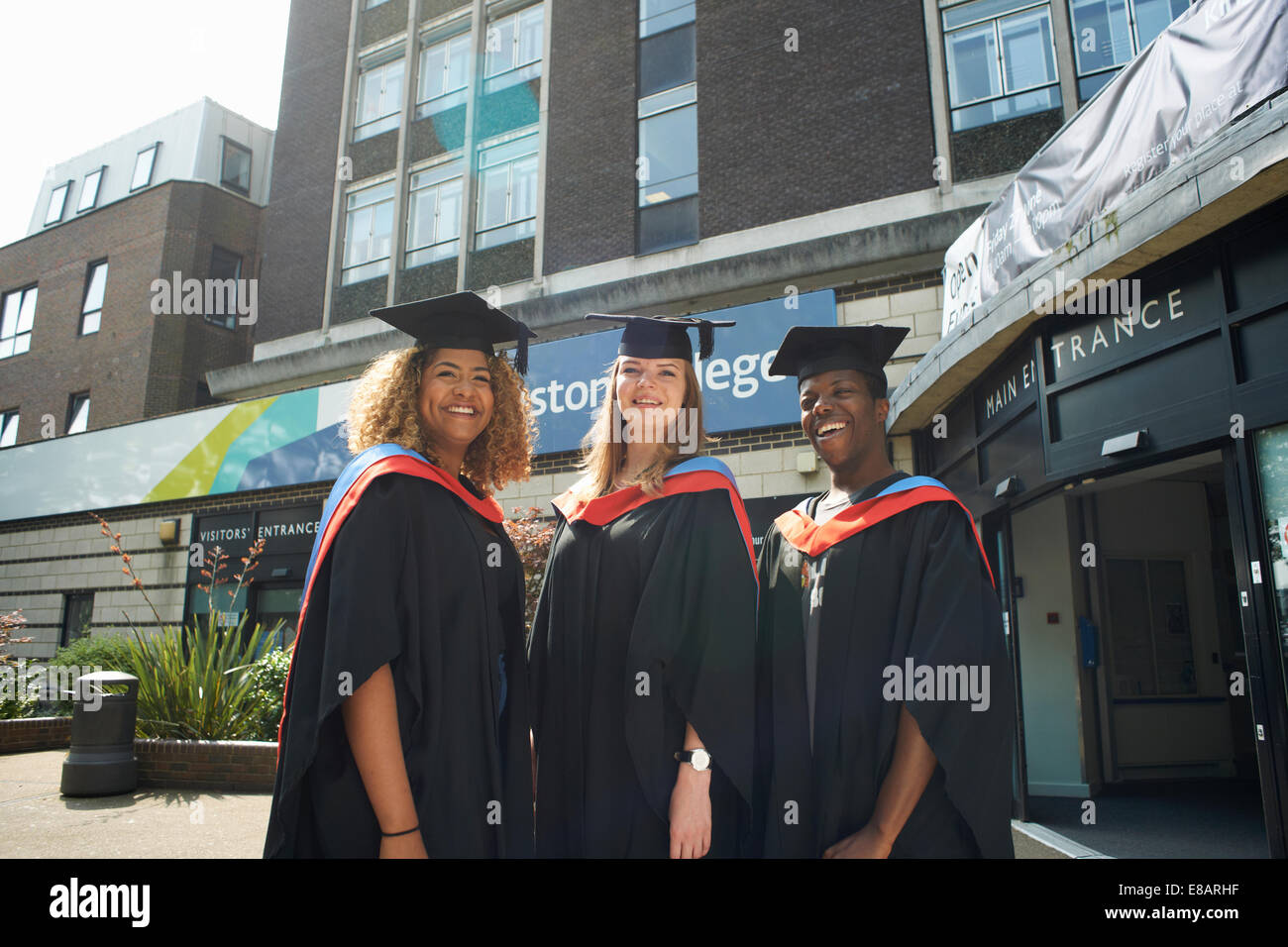 Portrait of three college students in graduation gowns and caps - Stock Image