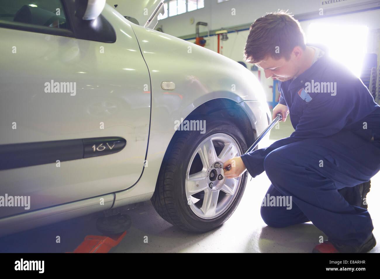 Male student mechanic tightening car wheel in college garage - Stock Image