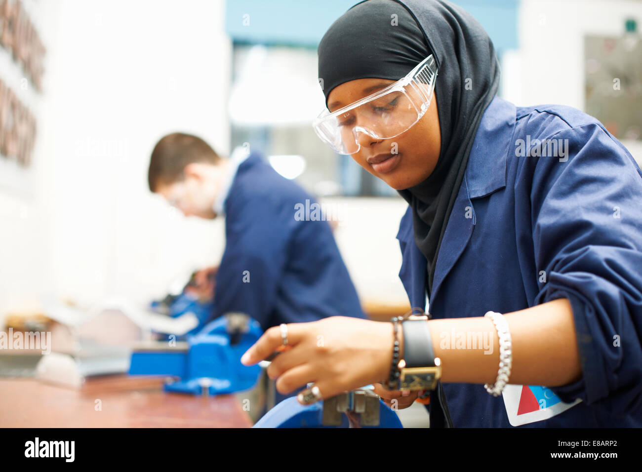 Female student using vice grip in college workshop - Stock Image