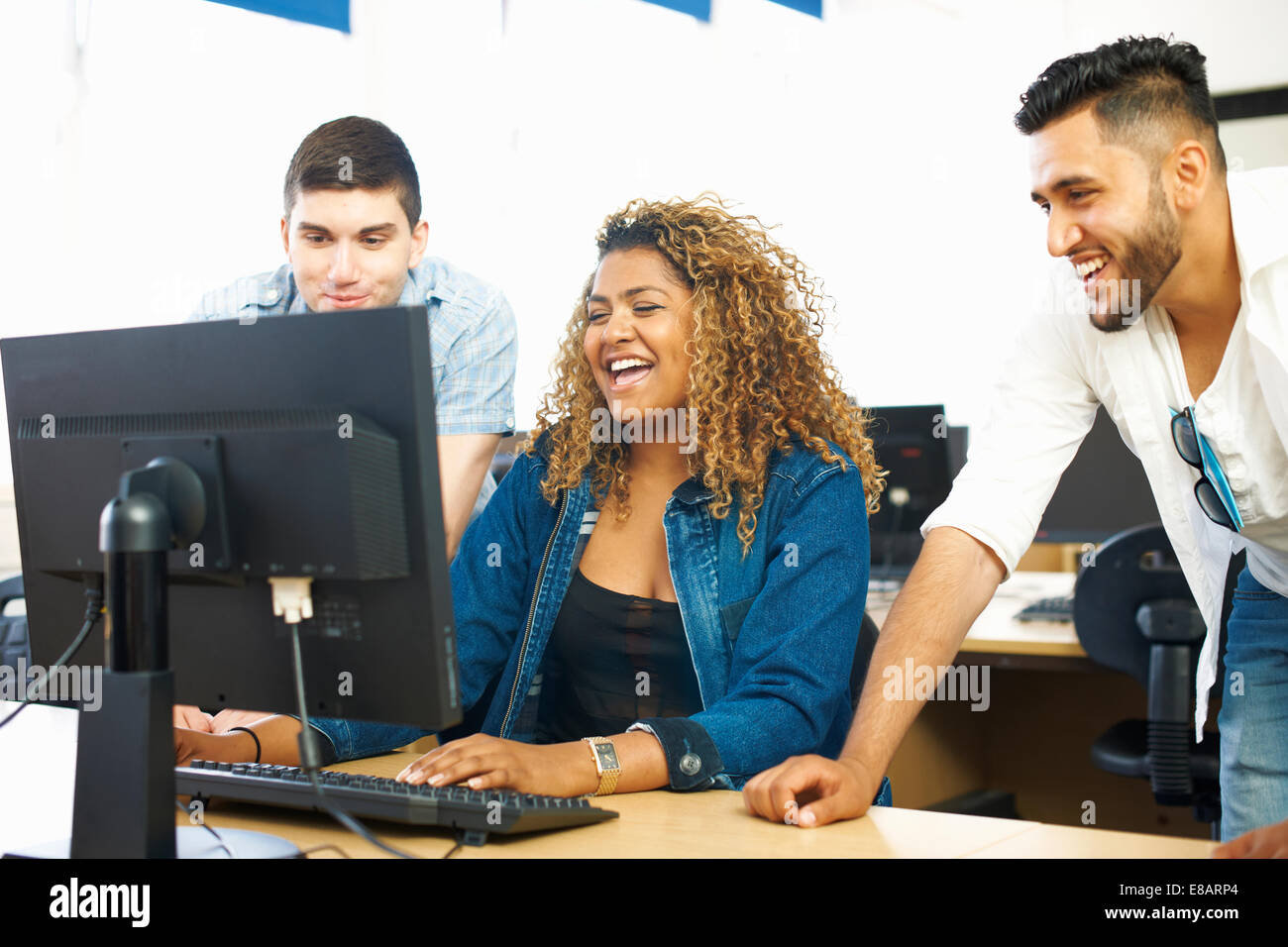 Three student friends laughing and looking at personal computer in classroom - Stock Image