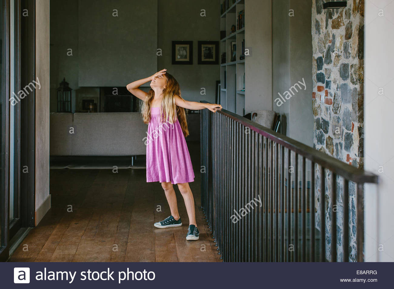 Girl on landing with hand on forehead - Stock Image