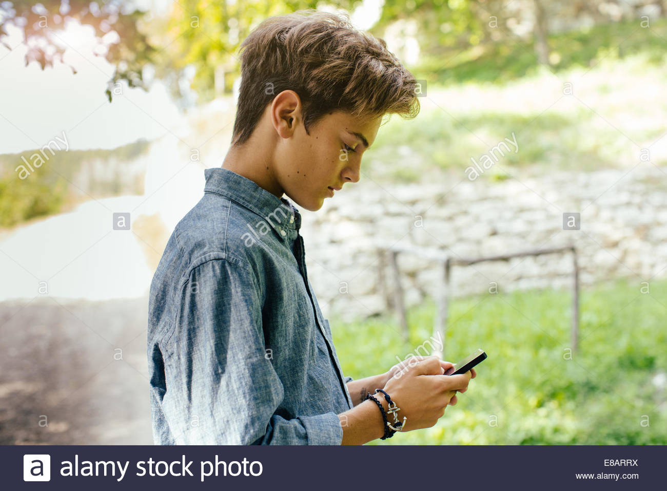Teenage boy using cell phone - Stock Image