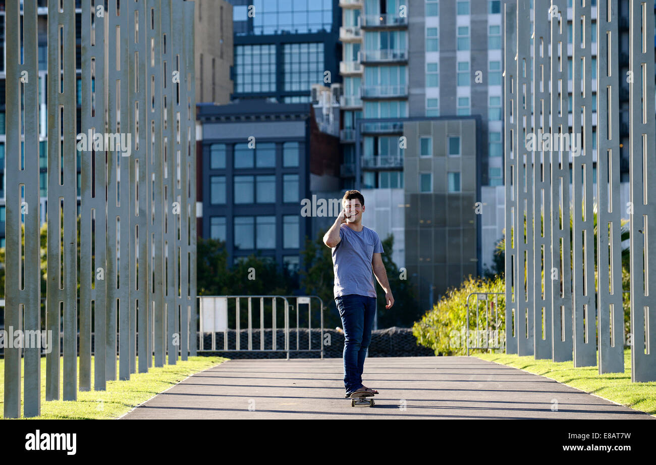 Young man on skateboard, using mobile phone Stock Photo