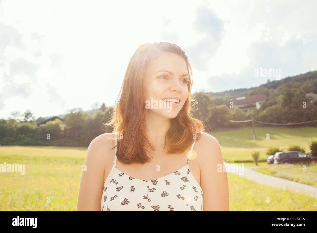 Young woman with brown hair, looking away - Stock Image