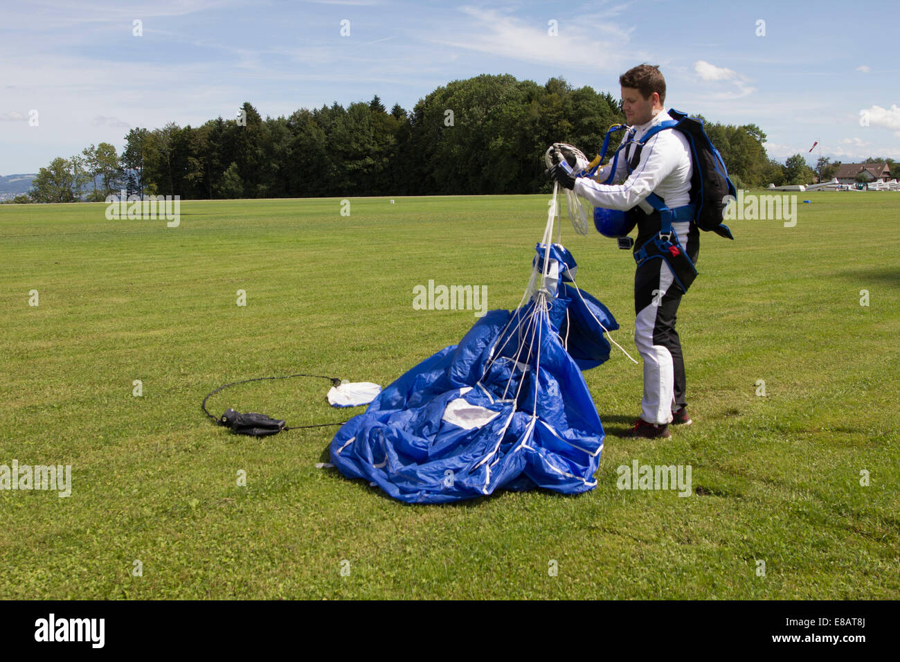 Male skydiver folding his parachute after skydive landing, Buttwil, Luzern, Switzerland - Stock Image