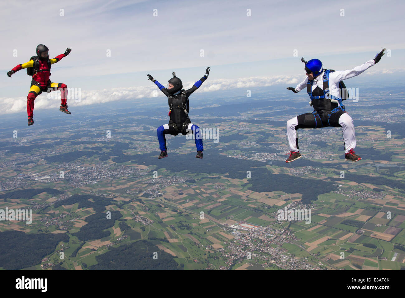 Team of three skydivers in sit fly position over Buttwil, Luzern, Switzerland - Stock Image