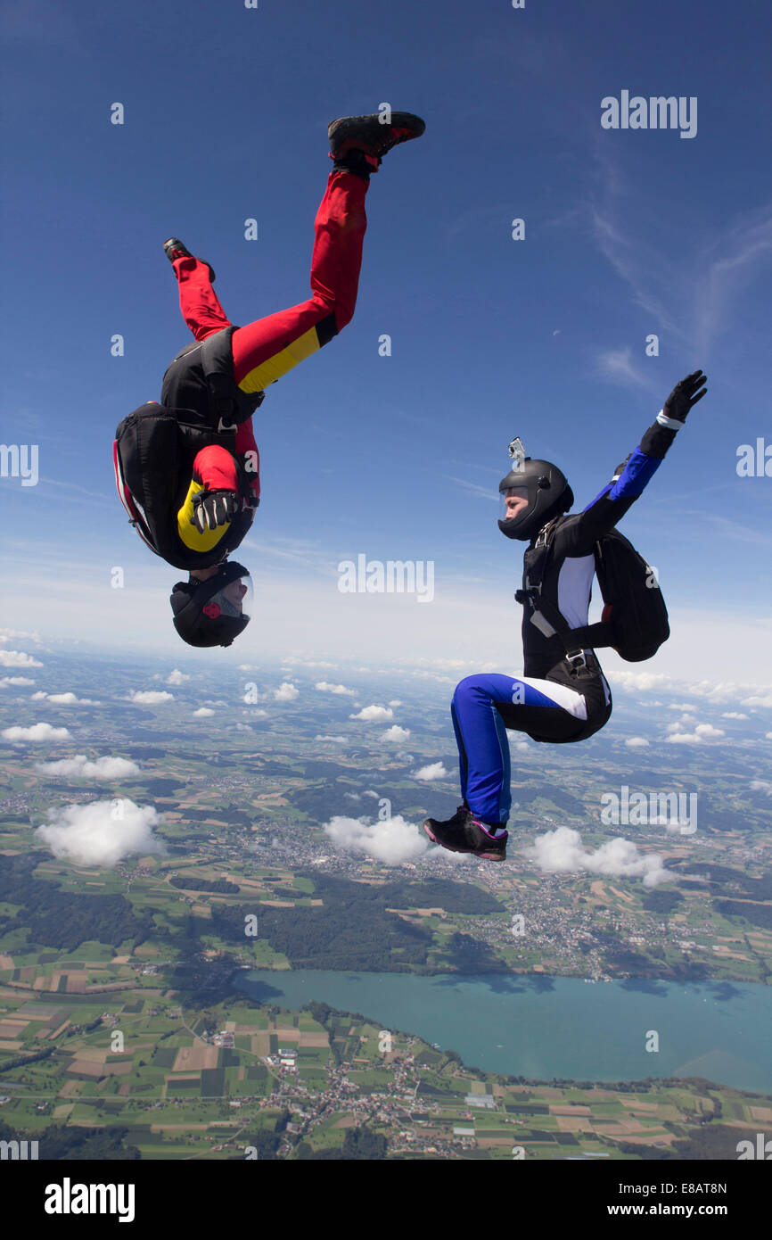Team of two female skydivers in sit fly and head down positions over Buttwil, Luzern, Switzerland - Stock Image