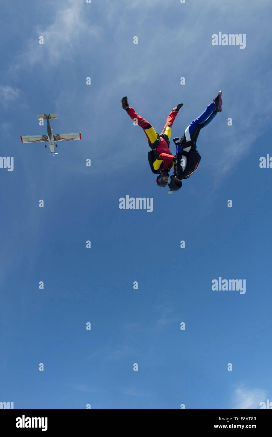 Team of two female skydivers in head down position over Buttwil, Luzern, Switzerland - Stock Image