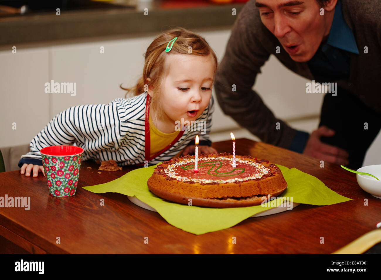 Young girl blowing out birthday candles on cake - Stock Image