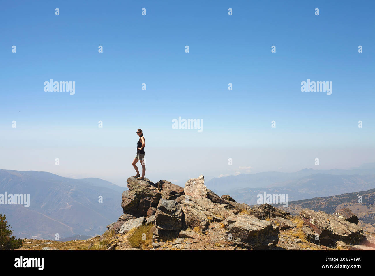 Young woman standing on top of rocks gazing at view, Sierra Nevada, Andalucia Granada, Spain - Stock Image