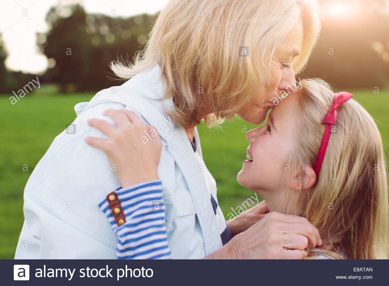 Grandmother kissing granddaughter on forehead - Stock Image