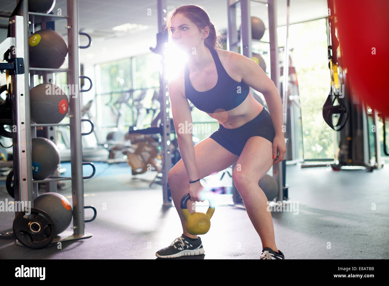 Young woman lifting kettlebell - Stock Image