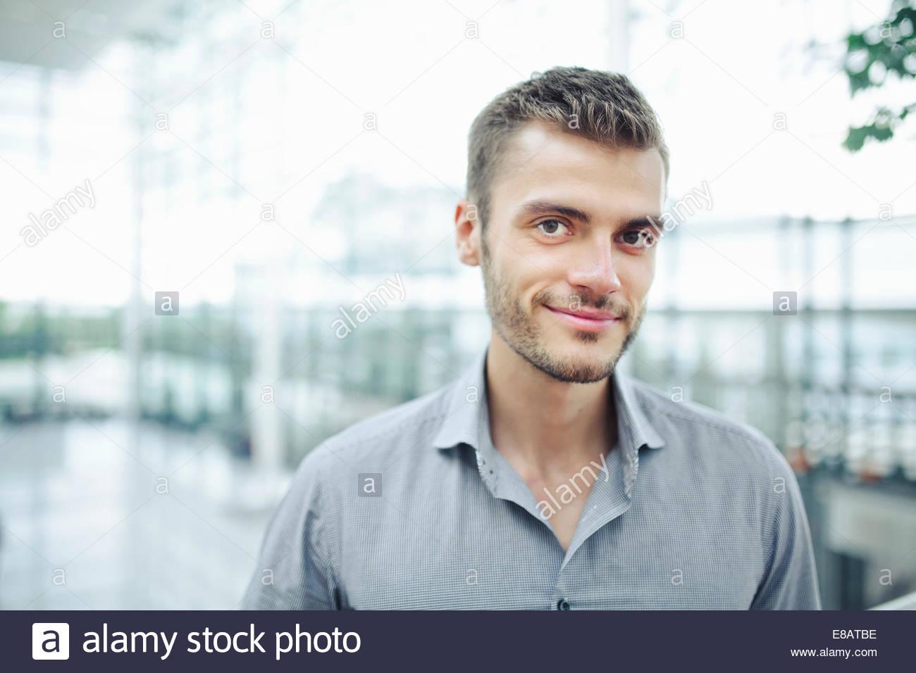 Young man wearing grey shirt, portrait - Stock Image