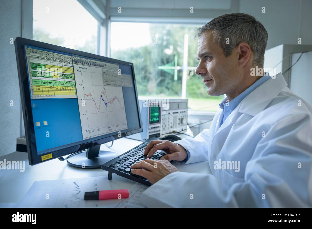 Scientist using computer to study electromagnetic interference results - Stock Image