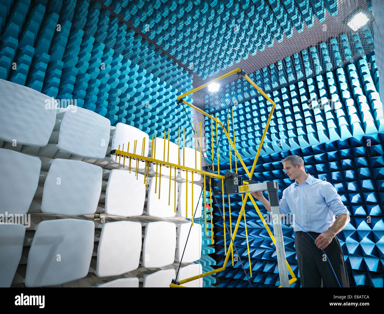 Scientist preparing to measure electromagnetic waves in anechoic chamber - Stock Image